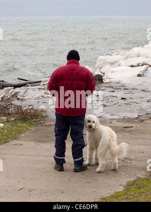 Man and his dog on lake shore. - Stock Photo