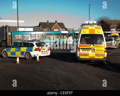 Police vehicles at the scene of a road traffic accident involving a bus in a village centre Marske Cleveland UK - Stock Photo