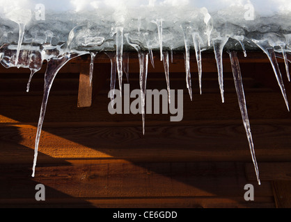 Icicles hanging from the eves of a house. - Stock Photo
