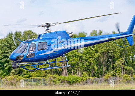 A Eurocopter Rotorcraft helicopter flies low to the ground. - Stock Photo