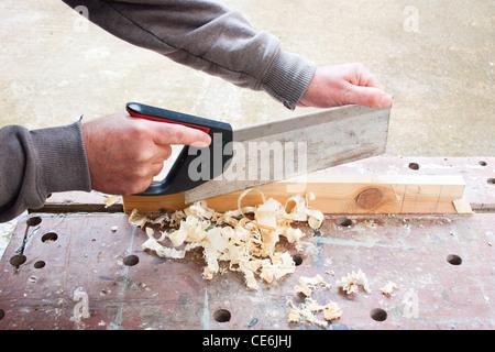 carpenter sawing wood - Stock Photo