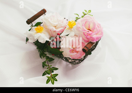 Camellia and rose flowers in a basket - Stock Photo
