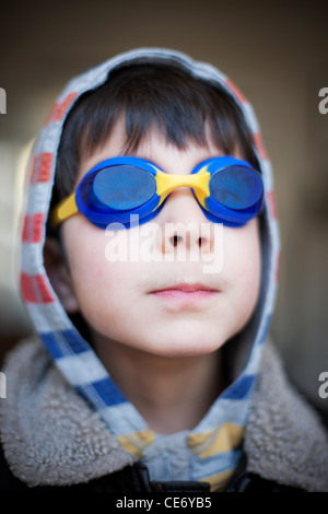 Boy wearing blue swimming goggles and hood - Stock Photo