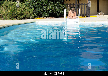 Stock photo of an 11 year old boy sat cross legged alone by the edge of a swimming pool. - Stock Photo