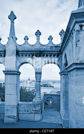 View of the Parliament (Orszaghaz) through the ramparts of Fishermen's Bastion (Halaszbastya), Budapest, Hungary. - Stock Photo