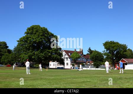 Cricket match in progress , Hand and Sceptre hotel in background , Southborough Common , near Tunbridge Wells , - Stock Photo