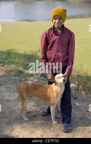 smiling young Indian boy with the village mongrel dog on a sunny winter day with a green lake in the background - Stock Photo