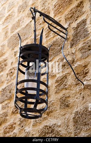 Old street light closeup on stone wall - Stock Photo