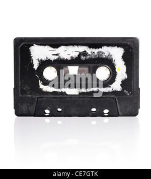 Old compact cassette audio tape with torn label - Stock Photo