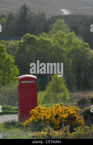 Old fashioned red telephone box in a countryside landscape, Sutherland, Scotland, UK - Stock Photo
