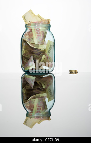 Glass jar full of hundreds of grivnas isolated on white background - Stock Photo