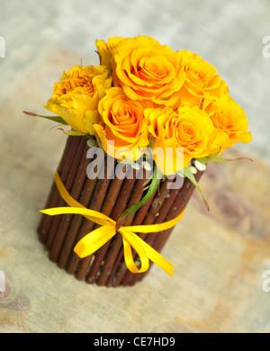 Beautiful small yellow roses in decorative flowerpot - Stock Photo