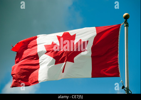Canadian National flag on flagpole blowing in breeze. - Stock Photo