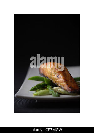 Teifi Salmon Fillet wrapped in Carmarthen Ham on a bed on wilted greens - Stock Photo