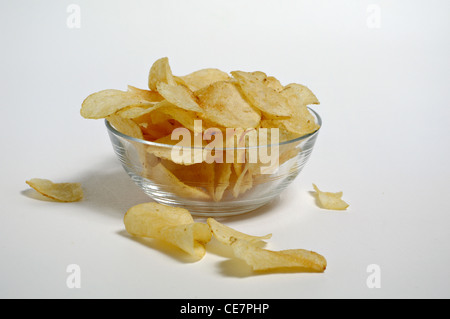 Potato chips sit in a glass bowl on a plain white background. - Stock Photo