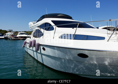 The white small yacht costs in a gulf at a pier - Stock Photo