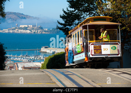 Street cable car, an iconic mode of transportation, going downhill to meeting Alcatraz Prison at the top of Hyde - Stock Photo