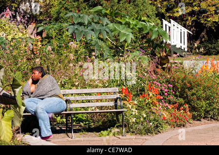 African American woman sitting on a park bench - Stock Photo