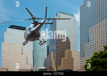 Helicopter flying between the scyscraper of manhattan south - Stock Photo