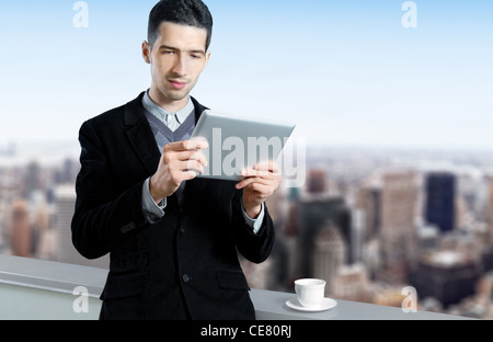 Young businessman with a cup of coffee uses a digital tablet on the roof of business center. Blurred cityscape with - Stock Photo