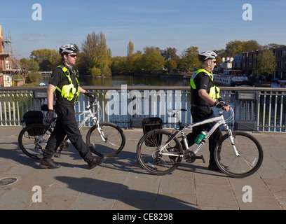 Two policemen in fluorescent jackets wheeling their bicycles across Windsor Bridge over the River Thames - Stock Photo