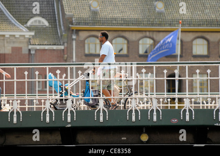 Man pushing baby in pushchair over a bridge in Leiden, Holland. - Stock Photo