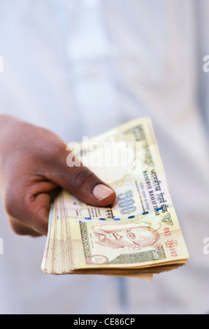 Indian mans hand holding a bunch of 500 rupee notes which were  demonetised in november 2016. India - Stock Photo