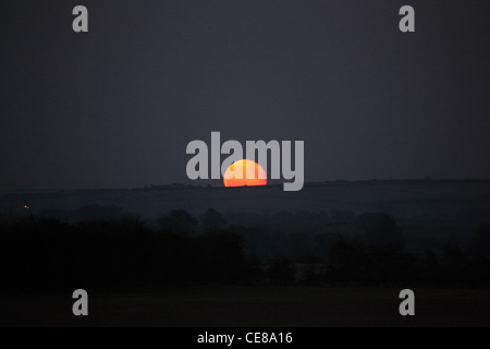 nearly full moon rising over horizon in the early evening light - Stock Photo