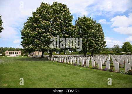 Memorial and graves under blooming chestnut trees in The Bayeux War Cemetery - The British War Cemetery at Bayeux, - Stock Photo