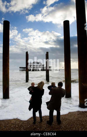 Couple with twins at the edge of the sea Old West Pier, Brighton, England - Stock Photo