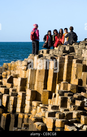 People climbing on the rocks at Giant's Causeway, Northern Ireland - Stock Photo