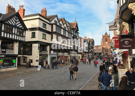 Busy pedestrianised cobbled street scene with shops in historic Tudor buildings in city town centre. Bridge Street - Stock Photo