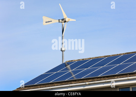 Windsave micro wind turbine and solar panels on a domestic eco home house roof for power generation with alternative - Stock Photo