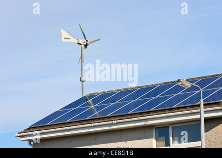 Windsave micro wind turbine and solar panels on a house roof providing cheap electricity alternative energy power - Stock Photo