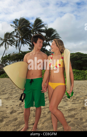 young couple at the beach with their surf boards - Stock Photo