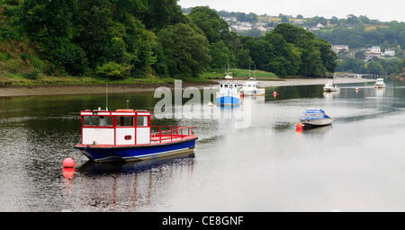 Boats moored up on the river Teifi, Cardigan with St Dogmeals in the background - Stock Photo