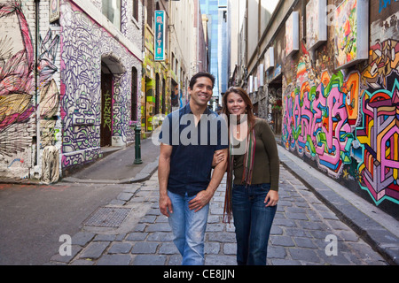 Young couple walking in city laneway, holding hands and looking at street art. Hosier Lane, Melbourne, Victoria, - Stock Photo