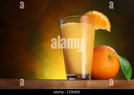 Oranges and glass of juice on a wooden table. - Stock Photo
