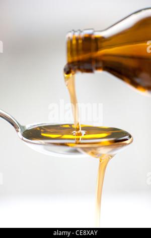 Pouring medicine. - Stock Photo