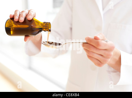 MODEL RELEASED. Pouring medicine. - Stock Photo