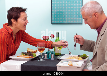 Photo of a mature couple dining in a restaurant, she is trying his pasta dish. - Stock Photo