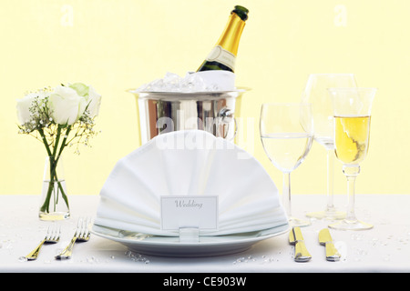 Photo of a wedding table place setting with place card and a bottle of chilled champagne in an ice bucket. - Stock Photo