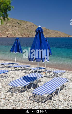 Empty sunloungers and umbrellas' on a pebble beach, Livadia, Tilos Island, Dodecanese, Greece - Stock Photo