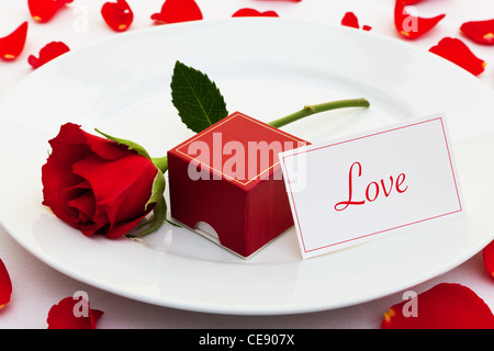 Photo of a red rose on a plate with a box for an engagement ring and a card with the word Love - Stock Photo