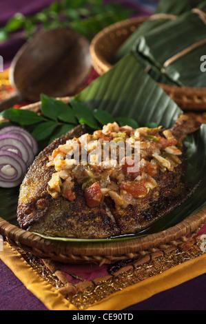 Pomfret fish cooked in banana leaf Coastal India Food - Stock Photo