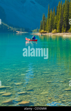 one man in a red hire canoe on Moraine Lake Banff national Park Alberta Canada North America - Stock Photo