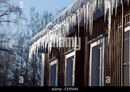 Icicles hanging from house eaves , Finland - Stock Photo