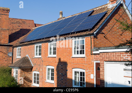 Seventeen solar panels on south-facing roof of old cottage in UK - Stock Photo