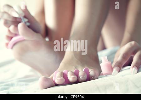 Woman doing foot nail treatment at home. Close-up photo - Stock Photo