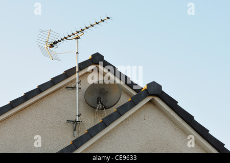 TV aerial and satellite dish on gable wall of modern house. - Stock Photo